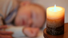 Sleeping baby boy in the candlelight closeup Stock Footage