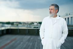 renowned scientist/doctor standing on the roof of the research c - stock photo