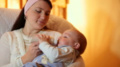 Young mother feeding baby boy milk formula from a bottle in the living room Stock Footage