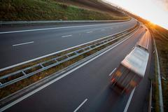 highway traffic - motion blurred truck on a highway/motorway/spe - stock photo