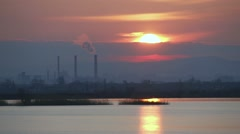 The sun sets over the lake with industrial chimneys-timelapse Stock Footage