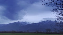 Winter landscape with snow-capped peaks and passing train Stock Footage