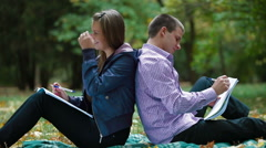 Two students studying in autumn park writes something in notebooks Stock Footage