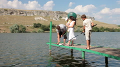 Young family with children spending weekend fishing by the lake Stock Footage