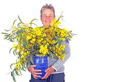 Beautiful mature woman with a bouquet of mimosa - stock photo