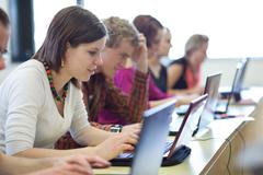young, pretty female college student sitting in a classroom full - stock photo
