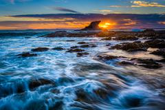 Waves and rocks at sunset, at Little Corona Beach, in Corona del Mar, Califor Stock Photos