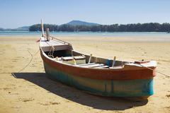 Boat on land in the area of sea tide - stock photo