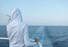 Young woman looking at the ocean from a fast going liner - stock photo