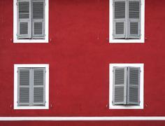 Red house facade with white windows (Corte, Corsica, France) Stock Photos