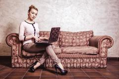 Stock Photo of Business woman using computer. Internet home technology. Vintage photo.
