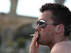 Deadly nasty habit - Male smoker wearing sunglasses smoking a ci - stock photo
