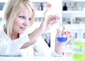 Closeup of a female researcher holding up a test tube and a reto Stock Photos