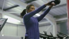 Focus pull from weight to young woman exercising with a kettle bell Stock Footage