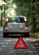 broken down car with warning triangle behind it waiting for assi - stock photo