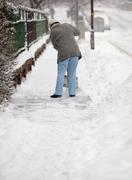 Woman shoveling snow from the sidewalk in front of his house aft Stock Photos