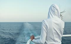 Young woman looking at the ocean from a fast going liner Stock Photos