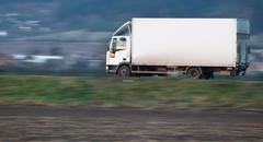 White delivery truck going fast on a road (panned image - motion Kuvituskuvat