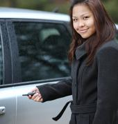 Young woman opening her new car - stock photo