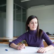 portrait of a pretty college student working in a classroom - stock photo