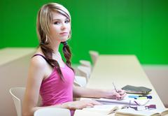 Portrait of a pretty young college student in a classroom - stock photo