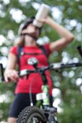 pretty young female biker outddors on her mountain bike (shallow - stock photo