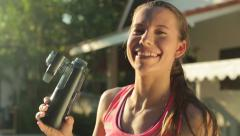 Woman drinking water after exercise Stock Footage