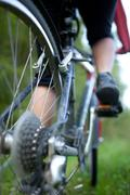 Biking - rear wheel of a young woman's mountain bike on a green Stock Photos