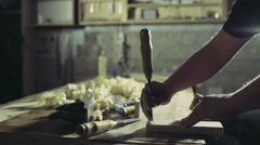 Joiner cuts a groove in the wooden workpiece with a chisel and hammer Stock Footage