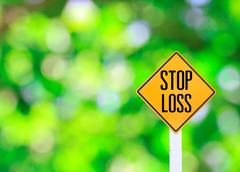 Yellow traffic sign text for stop loss green bokeh abstract light background Stock Photos