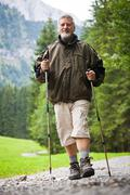 Active handsome senior man nordic walking outdoors on a forest p Stock Photos