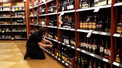 Worker exhibiting wine on the display rack. Stock Footage