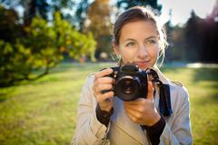 pretty female photographer outdoors on a lovely day - stock photo