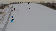 Families and children sledding downhill on a cold winters day Stock Footage