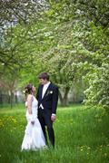 Stock Photo of young wedding couple - freshly wed groom and bride posing outdoo