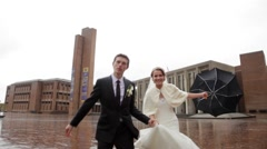 Runing bride and groom with umbrella Stock Footage