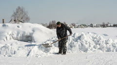 A man in camouflage clothing removes snow shovel Stock Footage