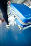 Airport rush: people with their suitcases walking along a corrid - stock photo