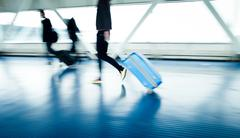 Airport rush: people with their suitcases walking along a corrid Stock Photos