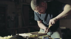 Joiner makes notches on the wooden workpiece with curved chisel Stock Footage