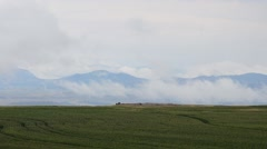 Clouds Roll Over Farm Fields with Mountains in the Background Stock Footage