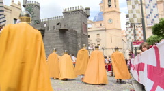 People with golden / orange capes walk to fake castle in parade Stock Footage