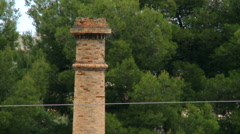 Top of red brick chimney with trees in background Stock Footage