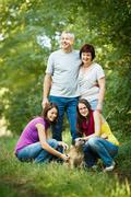Family portrait - Family of four with a cute dog outdoors Stock Photos