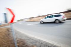 Traffic concept: car driving fast through a sharp turn (motion b - stock photo