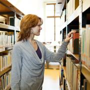 Stock Photo of pretty female college student in a llibrary (color toned image)