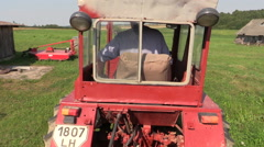 Farmer drive an old red tractor through meadow Stock Footage