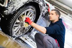 Man worker washing car's alloy wheels on a car wash Stock Photos