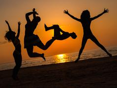 Silhouettes a young people jumping on a beach - stock photo