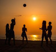 Silhouettes a young people playing with ball on a beach - stock photo